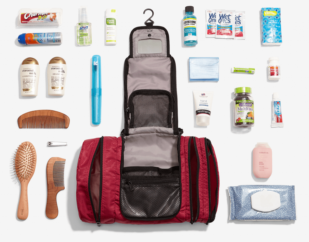 empty red hanging toiletry bag with items for your List for packing for a trip arranged around it