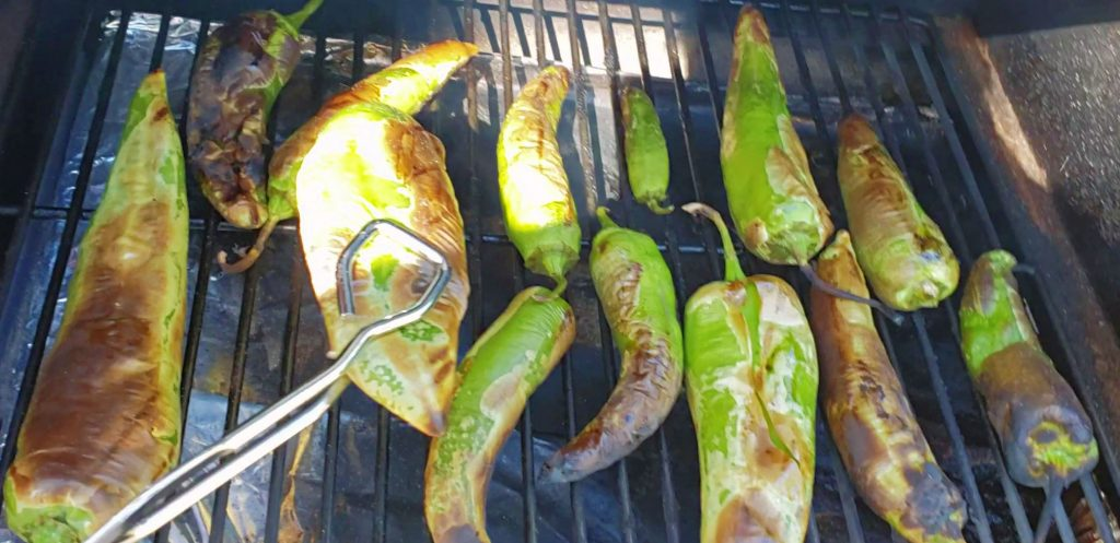 roast chilies lay on Traeger grill with tongs picking up one chile with blistered skin
