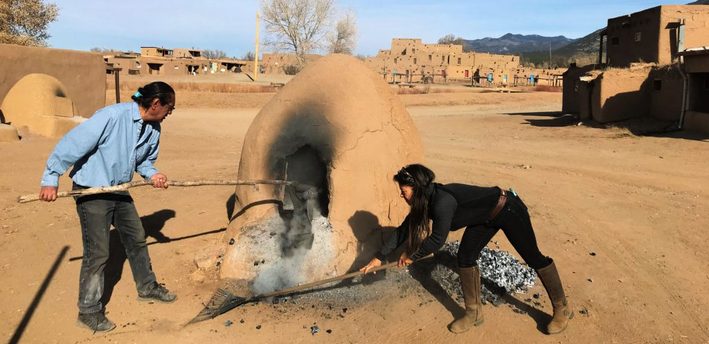 Man in blue shirt and woman in tall boots ten outdoor beehive-shaped adobe oven with the adobe walls of the Taos Pueblo in the background
