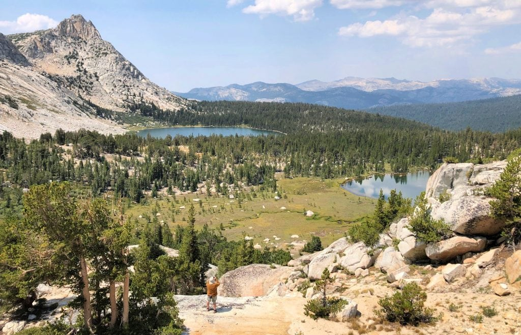 the man at the bottom of the picture looks very small compared to the expansive landscape of tall white mountains and a lake far below him