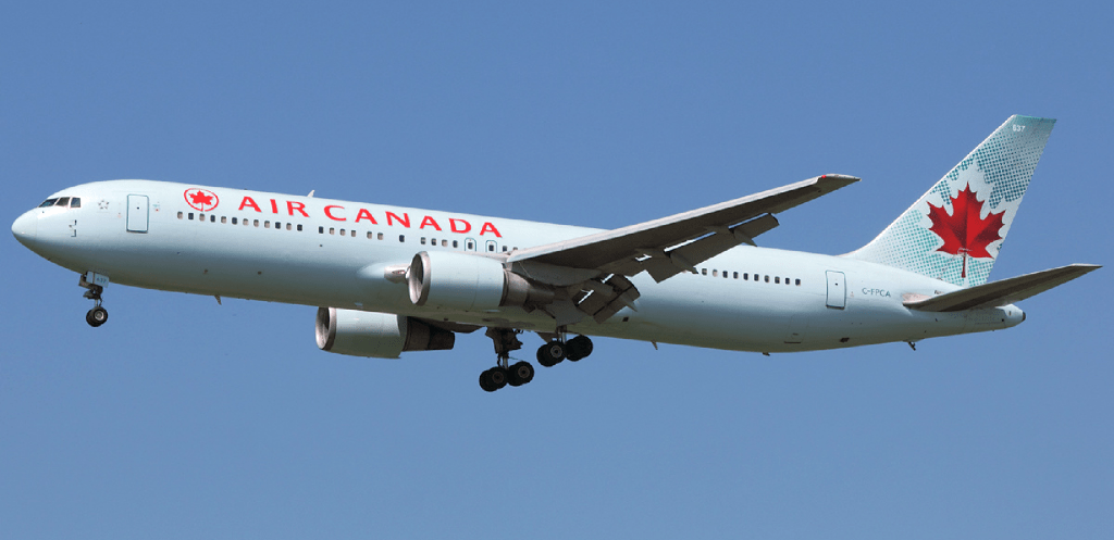 white airplane with red maple leaf on tail - flying in blue sky