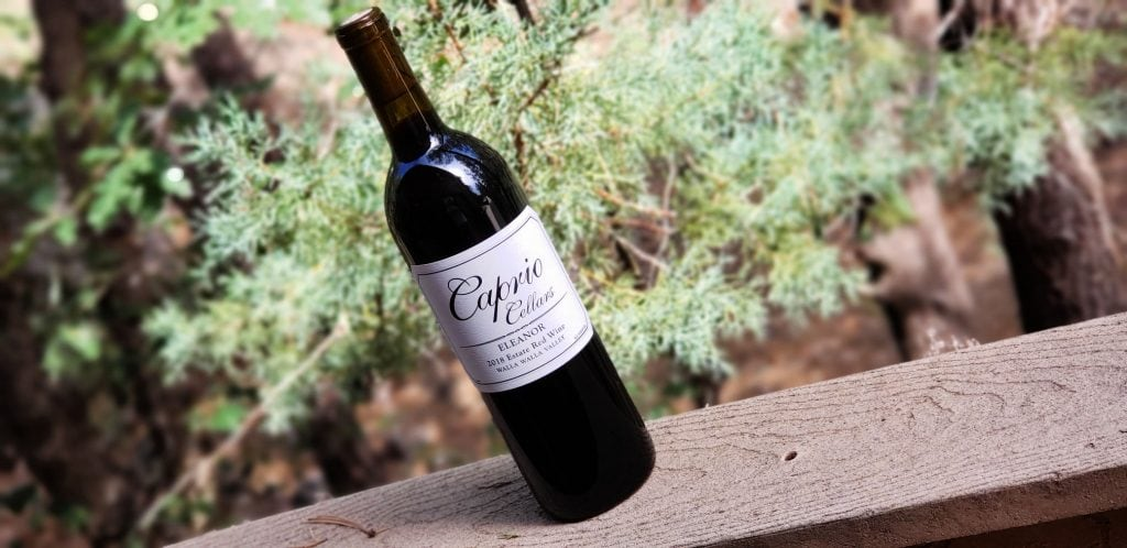 bottle of red wine with evergreen trees in background